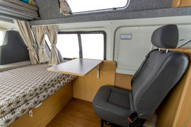 Comfy seat with desk inside Endeavour Campervan from Hippie Campers